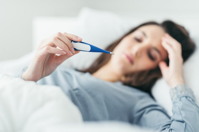 Woman in bed holding forehead and reading thermometer