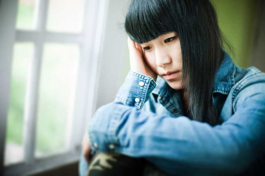 Depressed looking woman with bangs and jean jacket