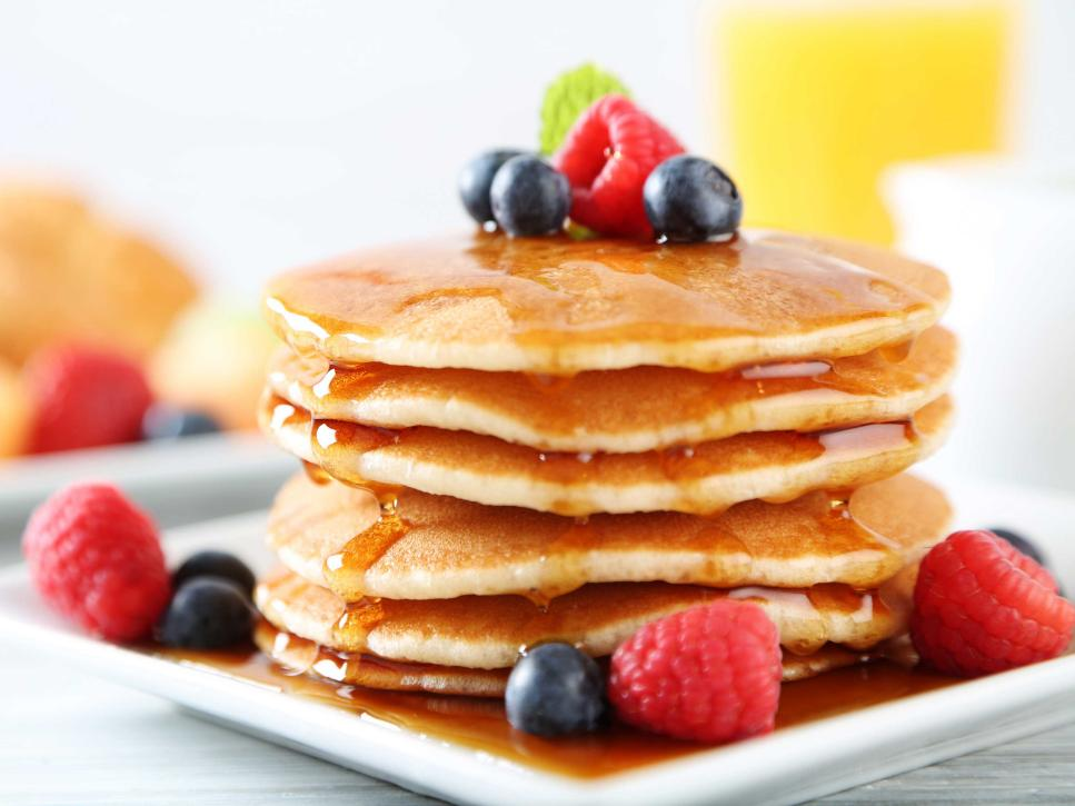 Stack of 6 pancakes with berries on top, covered with syup